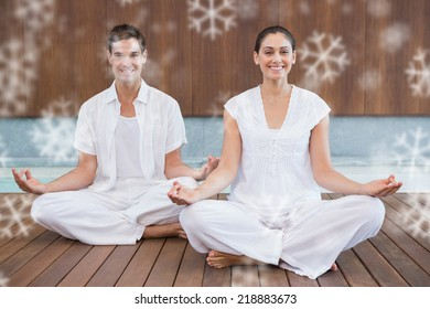 Attractive couple in white sitting in lotus pose smiling at camera against snowflakes