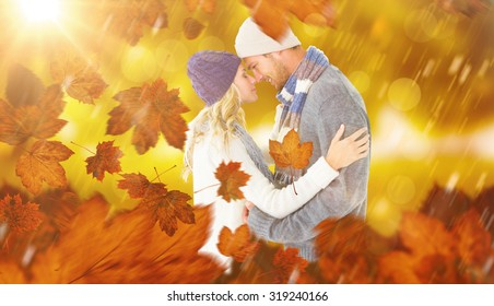 Attractive couple in winter fashion hugging against park