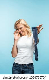 attractive curly blonde woman looking at smelly dirty sock on blue