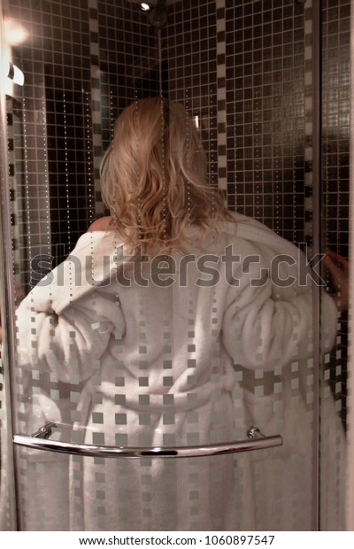 Attractive curly blonde woman turning from behind, taking off her white bathrobe in the blurred shower background