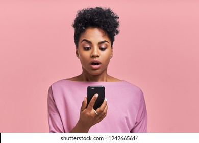 Attractive curly dark skinned female with Afro hairstyle looks agitated at screen of smartphone, impressed by message content received from friend, has surprised facial expression, stands indoor.