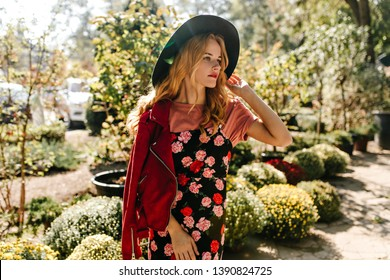 Attractive curly girl in wide-brimmed hat, red leather jacket and black dress with floral print looks thoughtfully into distance, enjoying spring day in garden