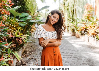 Attractive curly woman in orange skirt and white top looking at camera with smile. Girl with flower in her hair poses in botanical garden