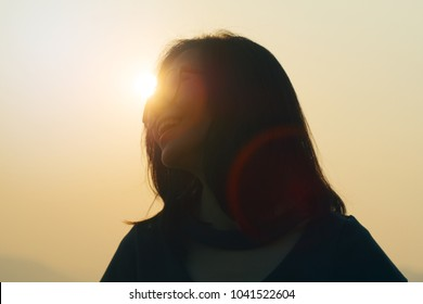 attractive cute asian young girl happy smiling. sunset moment. cute asian woman short hair with blurred background. hipster style. filtered image vintage tone. light and flare from sun