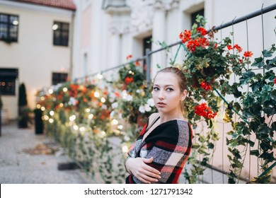 Attractive cute blondie girl posing in arranging flowers yard with lights. Sensual portrait of young beauty woman outdoors