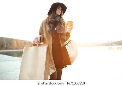 Attraktives süßes Mädchen mit Einkaufstaschen und warmen Getränken in der Hand