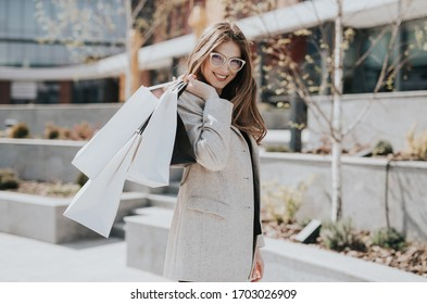 Attractive cute girl with the shopping bags and warm drink in her hand. Modern city megapolis on background. Lady order and shop online. Beautiful caucasian lady