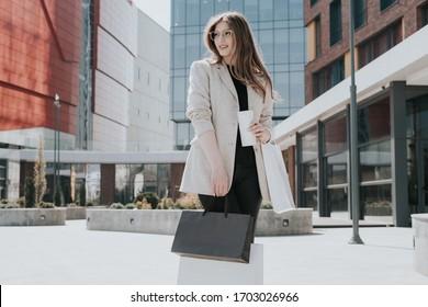 Attraktives süßes Mädchen mit den Einkaufstaschen und warmen Drinks in der Hand. Moderne Stadtmegapolis auf Hintergrund. Lady bestellen und online einkaufen. Schöne Kaukasierin