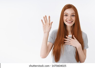 Attractive cute lovely redhead young girl blue eyes raise one hand hold palm heart promise give oath pledge loyalty swear not tell lie standing happily friendly look camera, white background