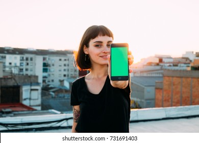 Attractive cute pretty young woman or teenager shows smartphone to camera, with green chroma key filled screen, smiles to camera, new generation millennial
