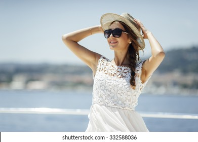 Attractive cute tanned girl on a yacht enjoy bright sun light on vacation