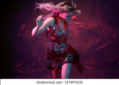 クラブ内の魅力的な踊りブロンド、ネオンライト、モーションエフェクト。黒い背景、長い露出