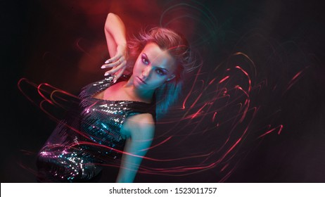 Attractive dancing blonde in the club, neon light, motion effects. Black background, long exposure