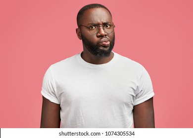 Attractive dark skinned male model frowns face, being discontent with work of colleagues, dressed in casual white t shirt, has fat figure, isolated over pink background. Ethnicity, facial expressions