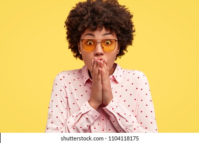 Attractive dark skinned young female freelancer keeps hands on mouth, looks with eyes full of disbelief, has curly dark hair, being puzzled with amount of work, isolated over yellow background