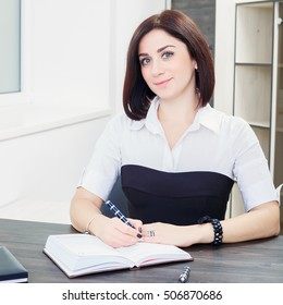 5af64c93d9d attractive dark-haired woman wearing a black and white blouse sitting at  the desk in