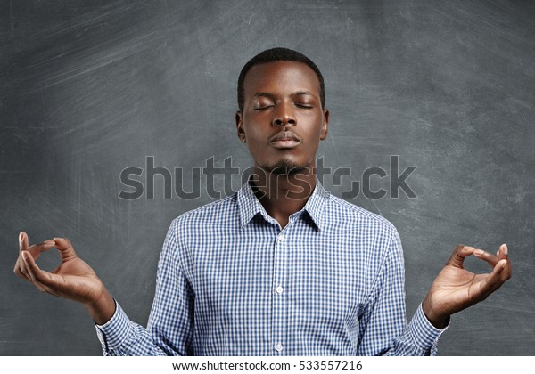 Attractive dark-skinned businessman with peaceful expression meditating, holding his hands in mudra gesture, keeping his eyes closed while practicing yoga in office, trying to calm down and relax