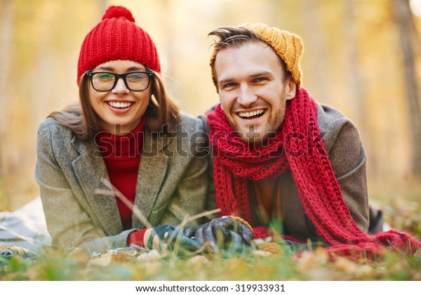 Attractive dates looking at camera with smiles while lying on ground in park