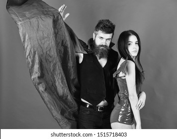 Attractive demon concept. Couple on strict face play role game. Vampire in cloak and sexy devil girl cuddling. Couple in love, perfect match. Man and woman dressed like vampire, demon, red background.