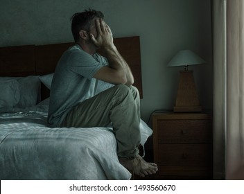 Attractive depressed and upset man at home bedroom . dramatic lifestyle portrait of 30s to 40s handsome guy sitting sad on bed feeling worried and desperate suffering depression problem