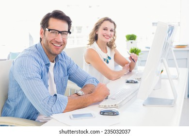 Attractive designers smiling at camera in office