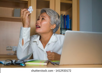 Attractive desperate and stressed middle aged Asian woman screaming gesturing overwhelmed and overwork working at office computer desk feeling exploited and upset in work stress