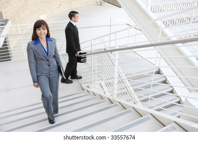 An attractive, diverse business man and woman  on stairs at office building