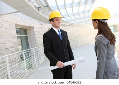 Attractive diverse man and woman architect team at building site
