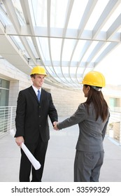 An attractive, diverse man and woman construction team shaking hands