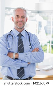 Attractive doctor with  his arms crossed standing