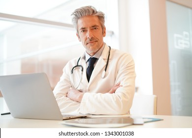 Attractive doctor looking at camera in hospital office