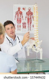 Attractive doctor showing a patient something on skeleton model in bright office