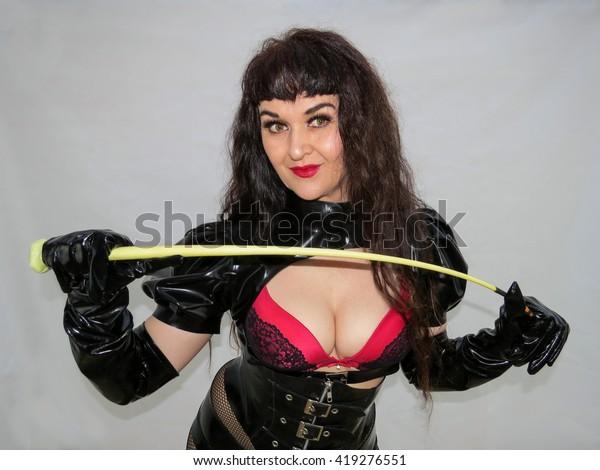 attractive-dominatrix-holding-whip-black