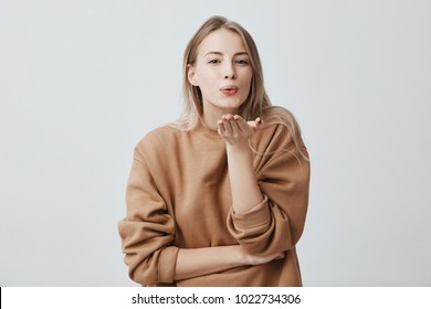 Attractive dreamy female model with blonde hair pouts lips, sends kisses to camera, poses against gray background. Beautiful charming woman with appealing appearance. Body language concept