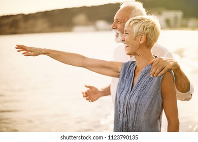 Attractive elderly couple enjoying sunset  at a beach. Side view. Horizontal.