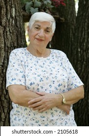 An attractive, elderly grandmother leaning against a tree with her arms folded.