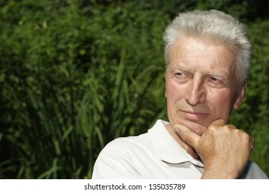 Attractive elderly man went to the river to relax