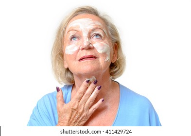 Attractive elderly woman applying a cosmetic cream, moisturizer or mask to her skin on her face and throat as she looks up into the air, close up on white