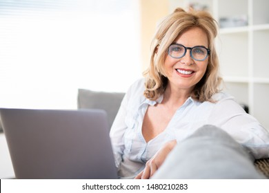 Attractive elderly woman indoors on the couch with laptop