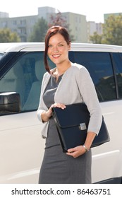 Attractive elegant business woman near luxury car hold briefcase calling