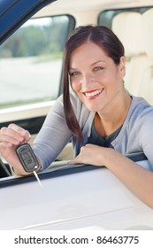 Attractive elegant businesswoman in new car showing keys smiling