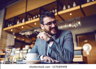 Attractive elegant caucasian smiling businessman in suit and with eyeglasses sitting in cafe and writing in agenda. In foreground is coffee in glass of water.