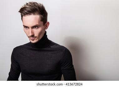 Attractive elegant man in black sweater posing on light gray background.