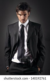 Attractive and elegant man posing with a gun in his trousers . Grey backdrop portrait