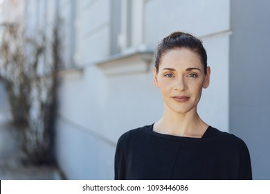 Attractive elegant woman with her hair in a neat bun standing outdoors looking thoughtfully at the camera in front of a house with copy space