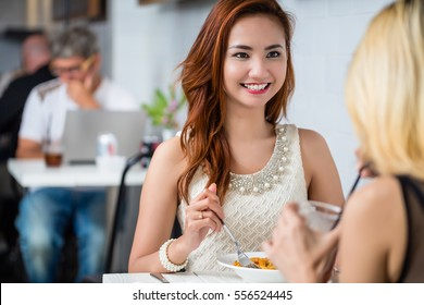 Attractive elegant young Asian woman having lunch with a friend at a restaurant sitting at the table together smiling and chatting, over the shoulder view