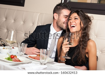 Attractive elegant young couple drinking a cocktail at the restaurant.