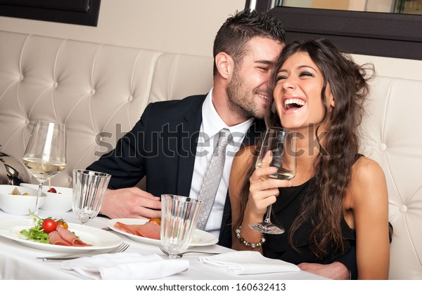 Joli jeune couple élégant buvant un cocktail au restaurant.