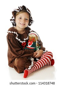 "An attractive elementary ""gingerbread girl"" happily sitting cross-legged with her gingerbread doll.  On a white background."