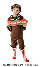 "An attractive elementary ""gingerbread girl"" holding a sign that points to Santa's Workshop.  On a white background."